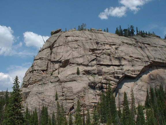 A gigantic rock outcropping known as Granite Dome stands silently against the blue sky.